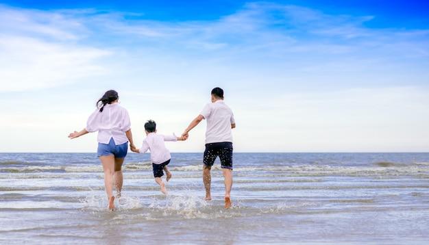 Familia feliz saltando en la playa
