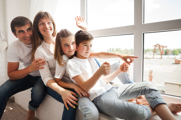 Familia feliz sentada en el alféizar de la ventana y jugando en casa