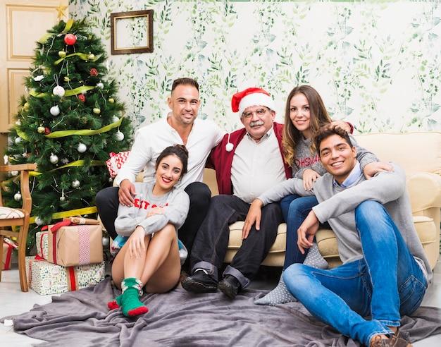 Familia feliz sentada cerca del árbol de navidad