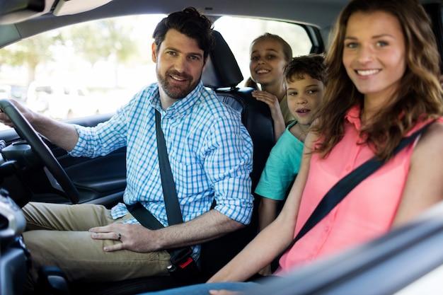 Familia feliz sentada en el coche