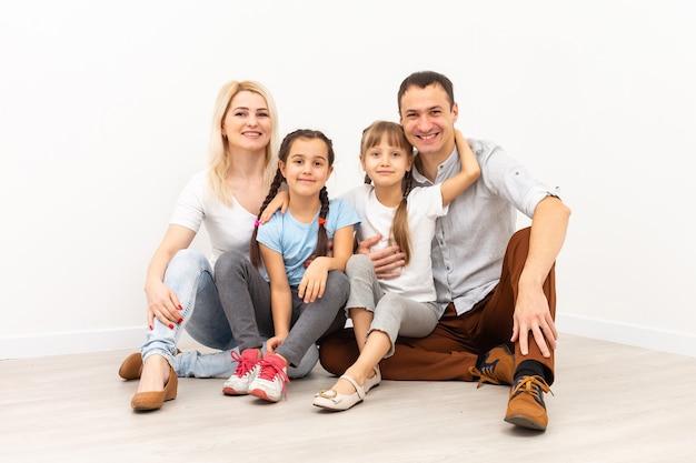 Familia feliz sentada en un piso de madera. padre, madre e hijo se divierten juntos. día de la mudanza, nuevo concepto de hogar