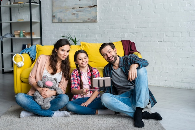 Familia feliz sentada en el piso
