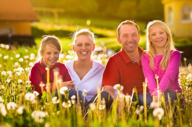 Familia feliz sentada en el prado de verano