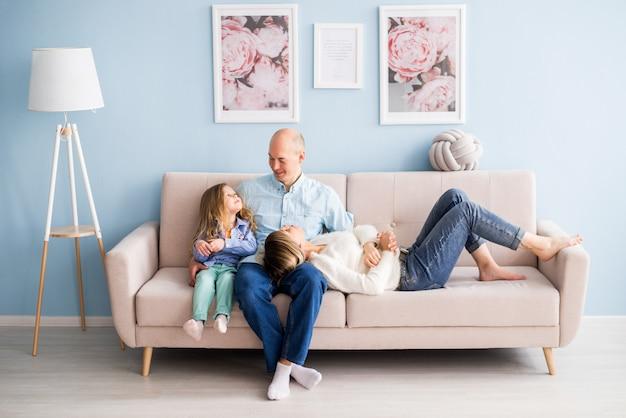 Familia feliz sentada en el sofá en casa