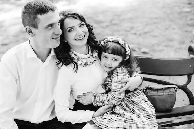 Familia feliz sentado en un banco en blanco y negro