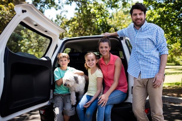 Familia feliz sentado en el baúl del auto con su perro