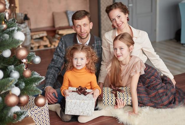 Familia feliz sentado cerca del árbol de navidad en la noche de navidad.