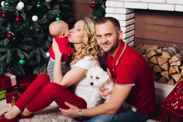 Familia feliz sentado junto a la chimenea con pequeño hijo y lindo perro y sonriendo