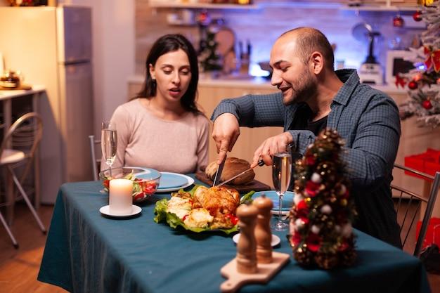 Familia feliz sentado en la mesa de comedor en la cocina decorada de navidad
