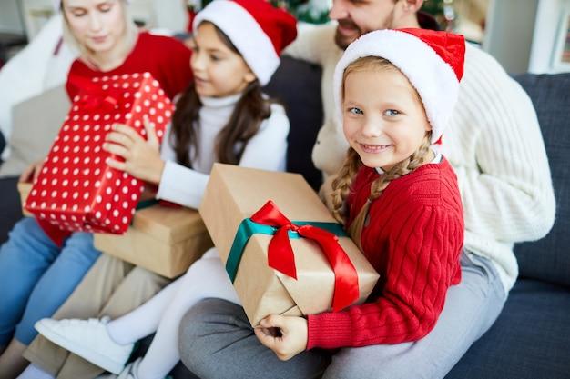 Familia feliz sentado en el sofá y desenvolver regalos de navidad