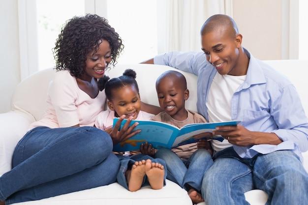 Familia feliz en el sofá leyendo el libro de cuentos
