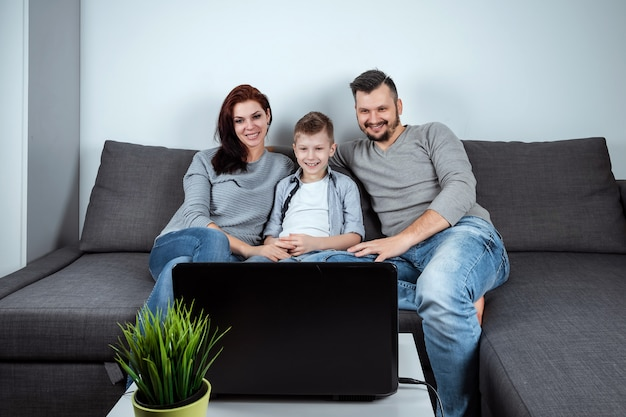 Una familia feliz con sonrisas viendo algo en una computadora portátil