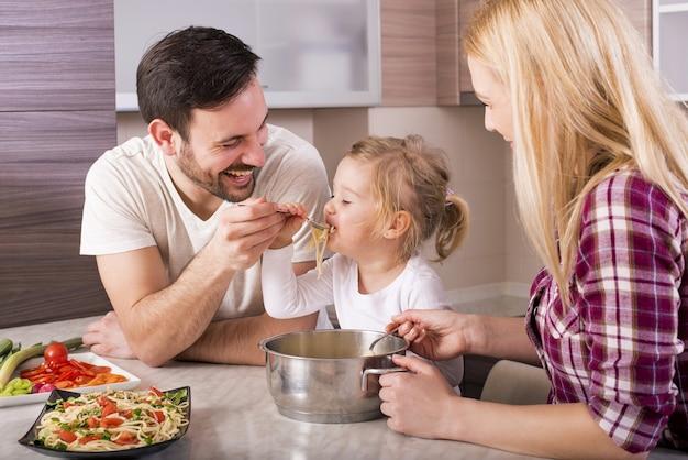 Familia feliz y su hija comiendo espaguetis en la encimera de la cocina