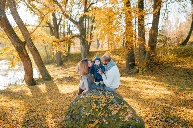 Familia feliz con su pequeño hijo en otoño parque en día soleado.