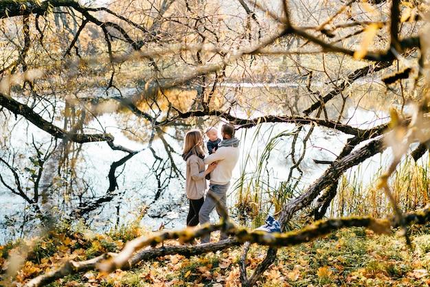 Familia feliz con su pequeño hijo en el parque otoño