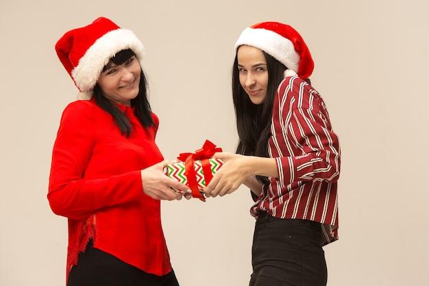 Familia feliz en suéter de navidad posando con regalos. disfrutando de abrazos de amor, gente de vacaciones. mamá y hija sobre un fondo gris en el estudio