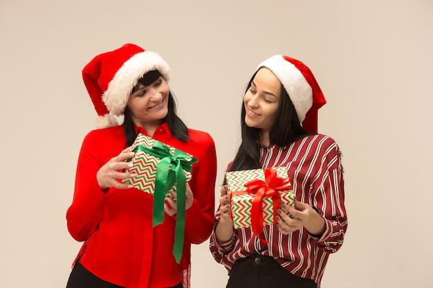 Familia feliz en suéter de navidad posando con regalos.