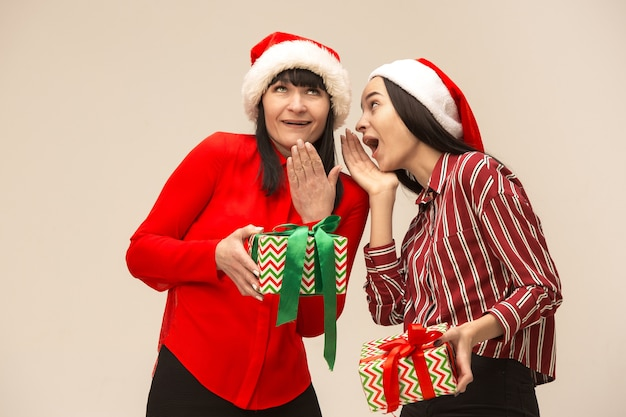 Familia feliz en suéter de navidad posando con regalos