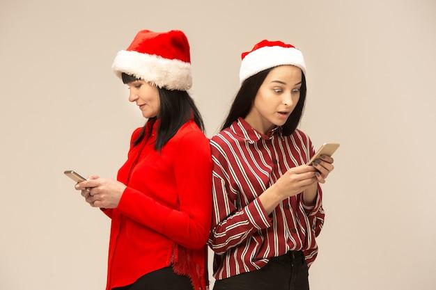 Familia feliz en suéter de navidad posando con teléfonos móviles. disfrutando de abrazos de amor, gente de vacaciones. mamá y hija sobre un fondo gris en el estudio
