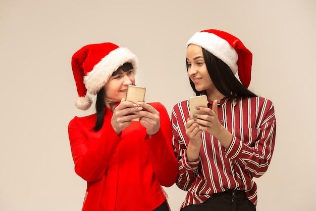 Familia feliz en suéter de navidad posando con teléfonos móviles.
