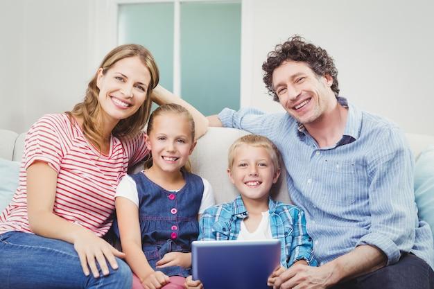 Familia feliz con tableta digital sentado en el sofá