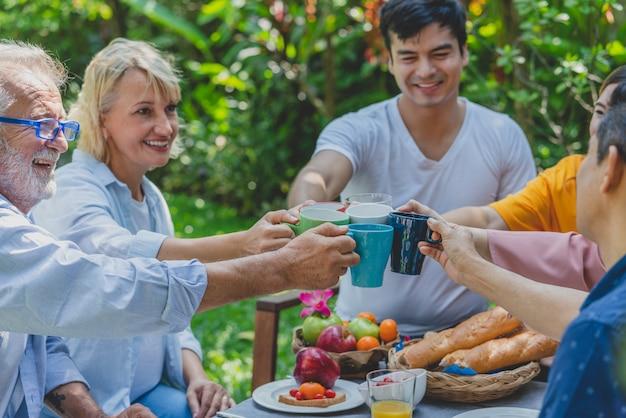 Familia feliz tintineo vasos mientras desayunan juntos en casa jardín