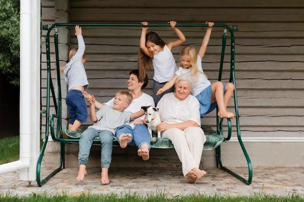 Familia feliz de tiro completo en columpio