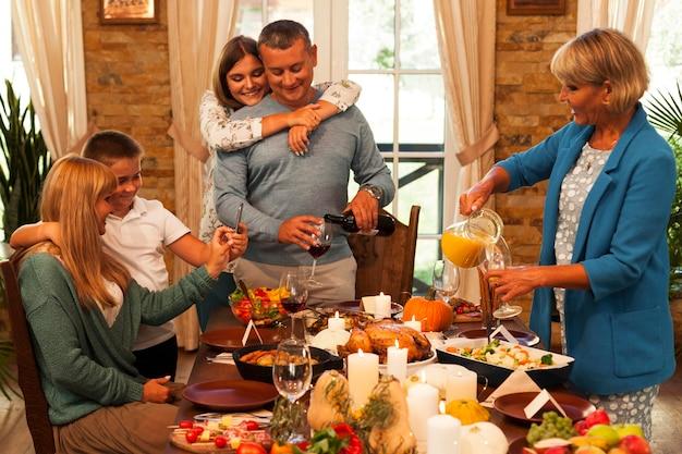 Familia feliz de tiro medio en la cena