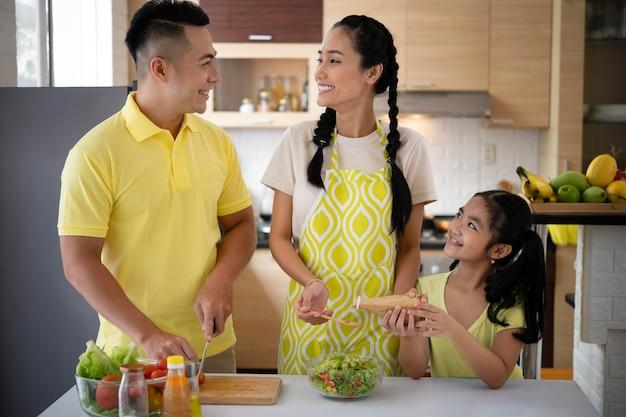 Familia feliz de tiro medio en la cocina