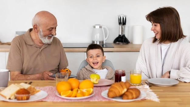 Familia feliz de tiro medio en la mesa