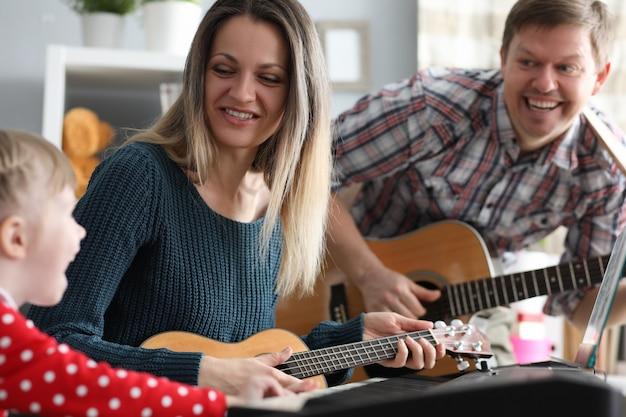 Familia feliz toca instrumentos musicales en el fondo