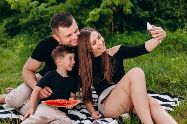 Familia feliz toma una foto selfie durante un picnic en el parque
