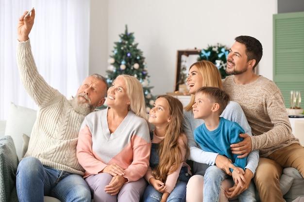 Familia feliz tomando selfie en habitación decorada para navidad