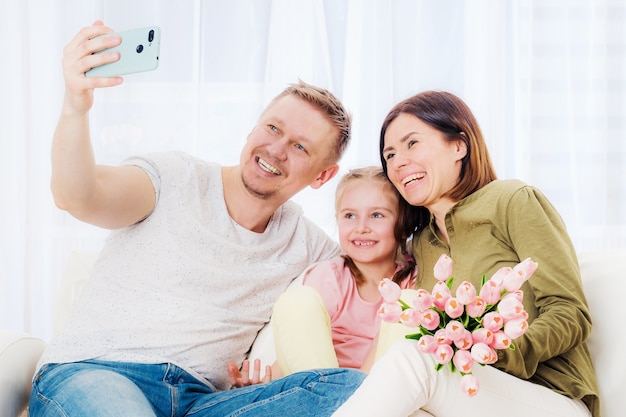 Familia feliz tomando selfie con regalos festivos en el día de la madre