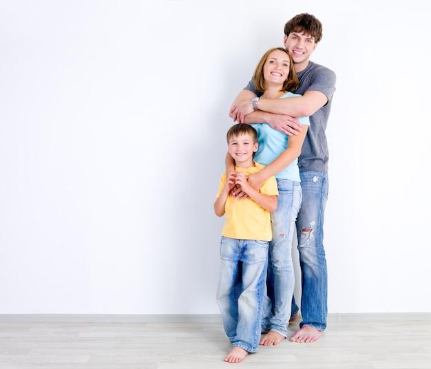 Familia feliz de tres personas de pie en abrazo cerca de la pared vacía