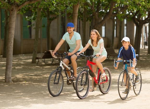 Familia feliz de tres que completa un ciclo en el camino de la calle
