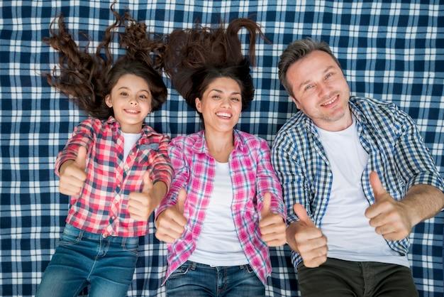 Familia feliz tumbado en la manta y mostrando el pulgar hacia arriba gesto