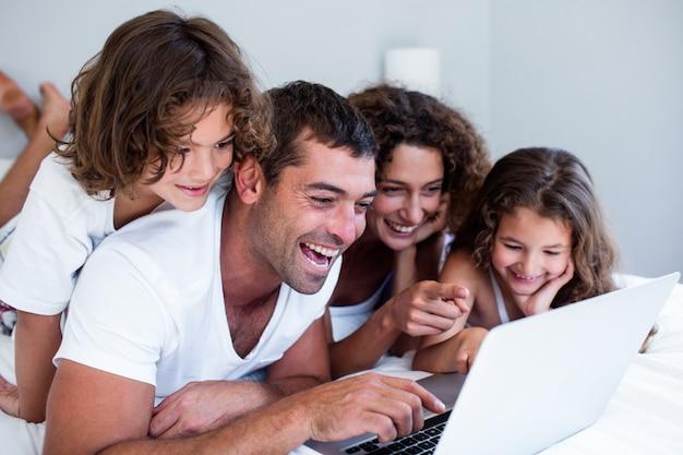 Familia feliz usando laptop juntos en la cama
