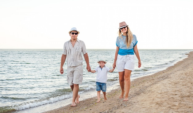 Familia feliz de vacaciones. mamá, papá y un hijo pequeño están caminando por la orilla del mar. familia viajera.