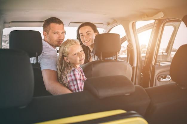 Familia feliz en un viaje por carretera en su coche.