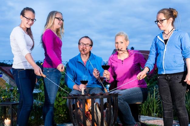 Familia en una fiesta de barbacoa en el jardín nocturno con salchichas y pan en un palo
