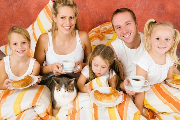 Familia y gato desayunando en la cama