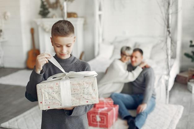Familia en una habitación. niño cerca de la decoración navideña. madre con padre con hijo