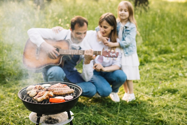 Familia haciendo una barbacoa en la naturaleza