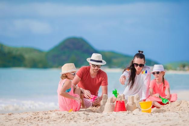 Familia haciendo castillos de arena en la playa blanca en vacaciones de verano