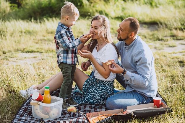 Familia haciendo un picnic y comiendo pizza en el parque