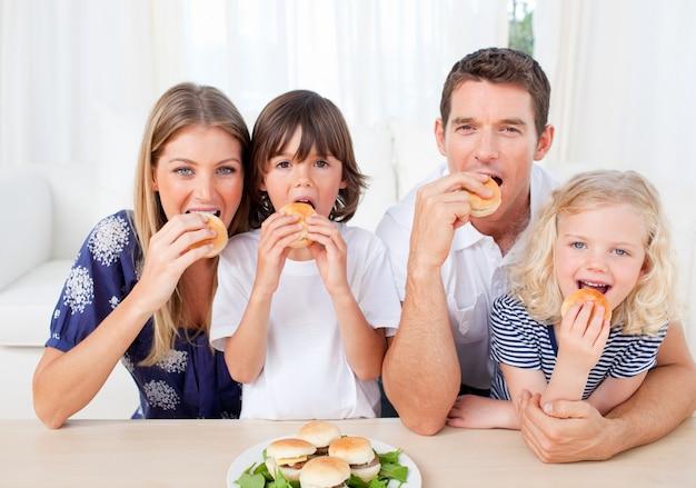 Familia hambrienta comiendo hamburguesas en la sala de estar