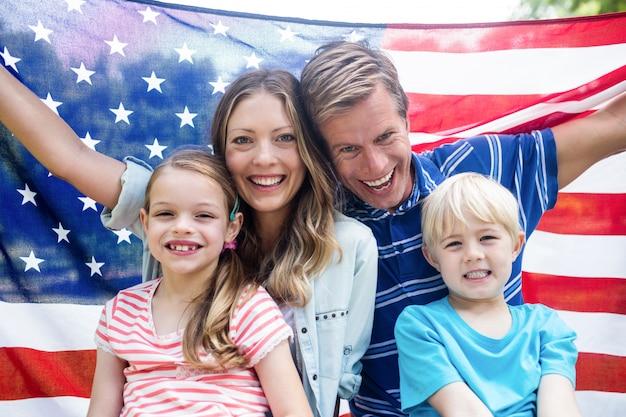 Familia hapy sosteniendo la bandera americana en el parque