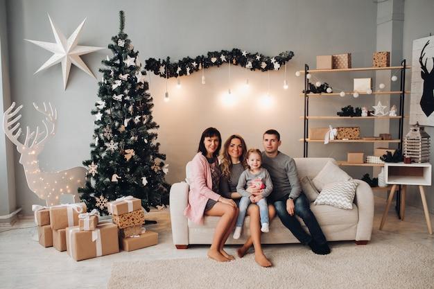 Familia en hermosa habitación decorada para navidad.