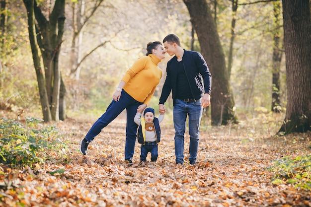 Familia hermosa joven caminando tomados de la mano por el parque de la ciudad. otoño. familia feliz y sus hijos caminando en el parque de otoño y pasar un buen rato.